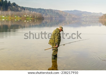 Senior fisherman fish in Solina Lake, Bieszczady, Poland - stock photo
