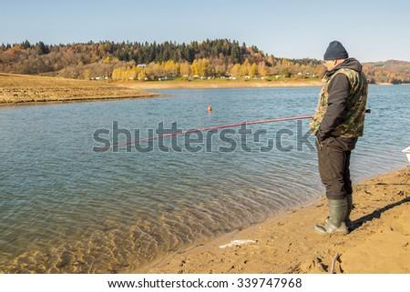Senior fisherman fishes in Solina Lake, Bieszczady, Poland - stock photo