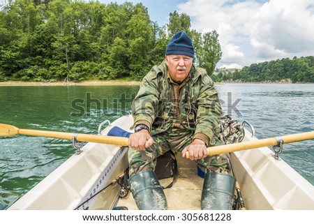 Senior fisherman paddling on Solina Lake in Poland - stock photo