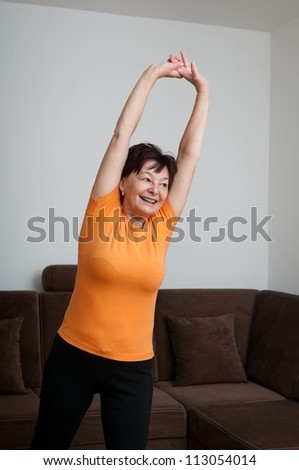 Senior fitness woman exercising at home - stock photo