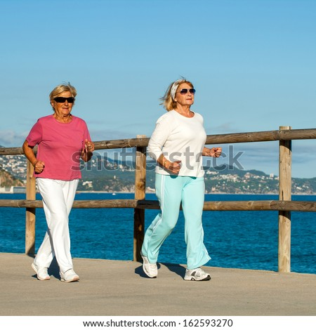 Senior fitness women jogging together at beachfront.