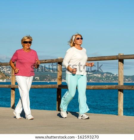 Senior fitness women jogging together at beachfront. - stock photo