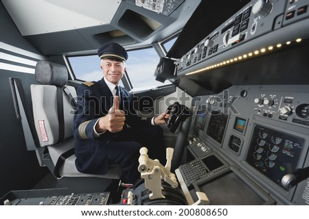 Senior flight captain with thumbs up in airplane cockpit - stock photo