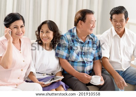 Senior friends socializing at home - stock photo