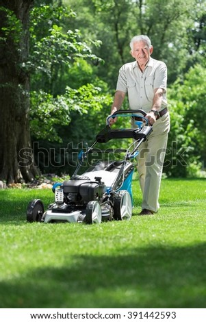 Senior gardener mowing his green lawn in garden