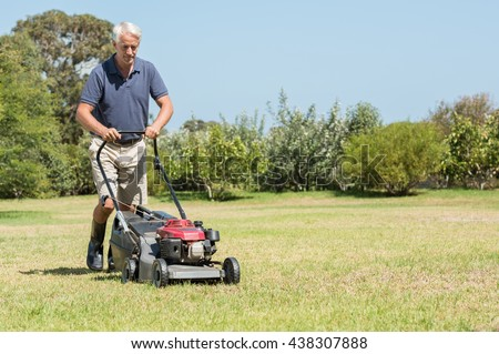 Senior gardener mowing his green lawn in garden. Man working in garden cutting grass with lawn mower. Retired mature man in shorts mowing grass with an electric mower in garden. - stock photo