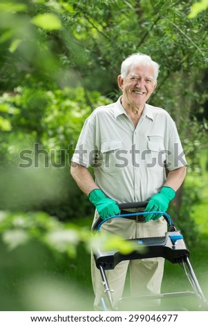 Senior gardener mowing the grass in backyard