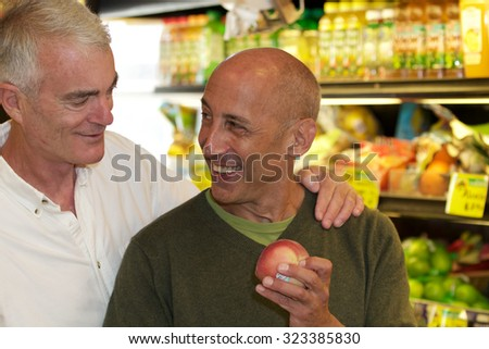 Senior Gay Male Couple Shopping for Produce in Grocery Store - stock photo