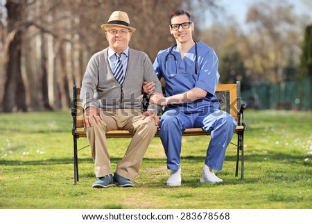 Senior gentleman and a young male nurse sitting on a bench and posing in a park - stock photo