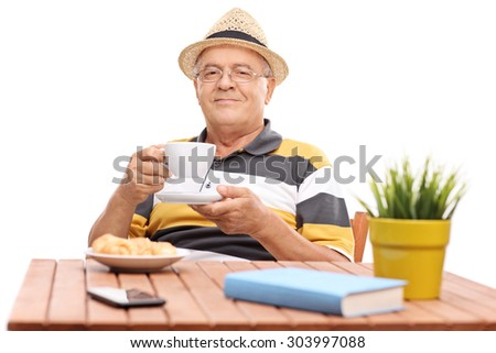 Senior gentleman drinking coffee seated at a wooden table with a few croissants on a plate in front of him isolated on white background