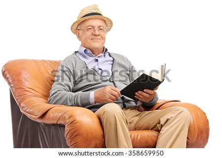 Senior gentleman holding a book seated in an armchair and looking at the camera isolated on white background - stock photo