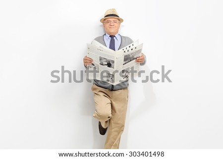 Senior gentleman holding a newspaper and leaning against a gray wall. The newspaper is custom made, text is Latin and the pictures are my copyright. Additionally property release uploaded.  - stock photo