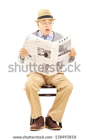 Senior gentleman in shock on a wooden chair reading a newspaper isolated on white background - stock photo