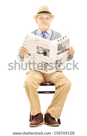 Senior gentleman on a wooden chair holding a newspaper and looking at camera isolated on white background - stock photo
