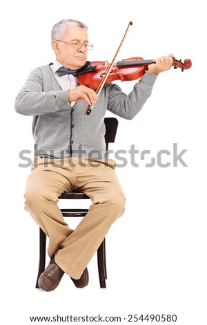 Senior gentleman playing a violin seated on a chair isolated on white background - stock photo