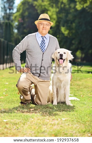 Senior gentleman posing in the park with his dog on green grass - stock photo