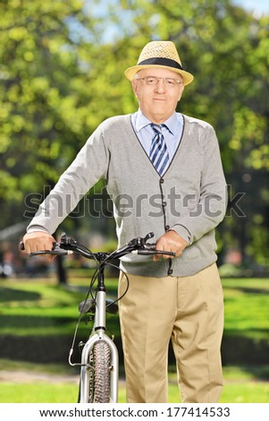 Senior gentleman pushing a bike in park