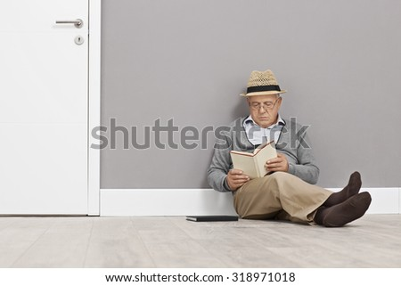 Senior gentleman reading a book seated on the floor and leaning against a wall next to a white door - stock photo