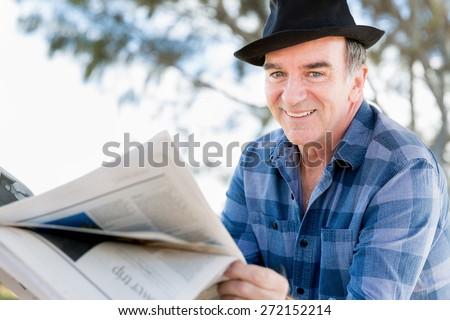 Senior gentleman reading newspaper in park - stock photo