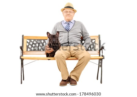 Senior gentleman seated on a bench with his dog isolated on white background - stock photo
