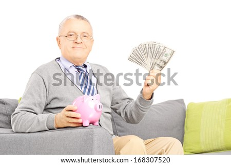 Senior gentleman seated on a sofa holding a piggy bank and US dollars isolated on white background - stock photo