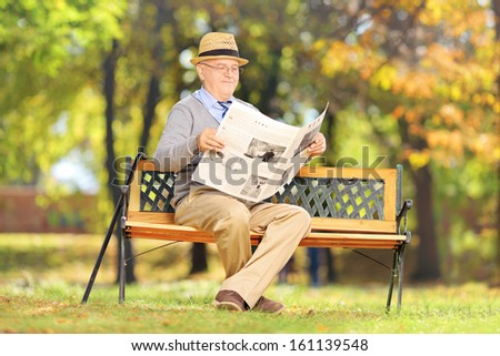 Senior gentleman seated on a wooden bench reading a newspaper in a park - stock photo