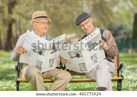 Senior gentleman showing something in the newspaper to a friend seated on a wooden bench in a park - stock photo
