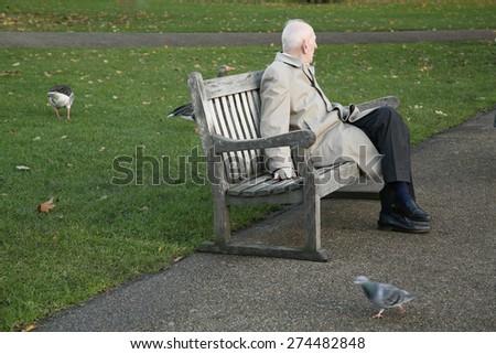 Senior gentleman sitting legs crossed on the bench in park - stock photo