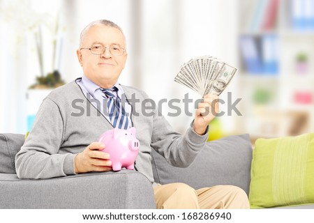 Senior gentleman sitting on a sofa and holding a piggy bank and money at home - stock photo