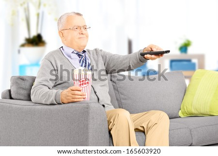 Senior gentleman sitting on a sofa and watching TV  - stock photo