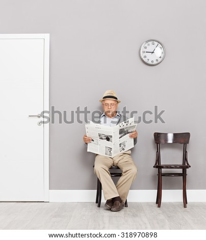 Senior gentleman sitting on wooden chairs in a waiting room and reading a newspaper shot with tilt and shift lens - stock photo