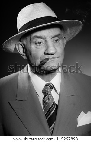 Senior glamour vintage man wearing suit and tie and hat. Black and white studio shot. Gangster look. Smoking cigar and drinking glass of whisky. Isolated. - stock photo