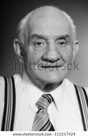 Senior glamour vintage man wearing white shirt, tie and striped braces. Black and white studio shot. Gangster look. Isolated. - stock photo
