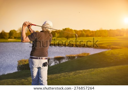 Senior golf player shooting ball at sunset, with lake in background. - stock photo