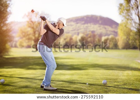 Senior golf player teeing off with golf club at sunset. - stock photo