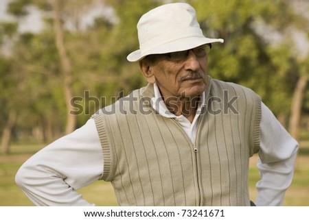senior golfer playing golf on a sunny evening. - stock photo