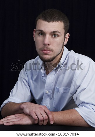 Senior graduate photo of young male with facial hair wearing blue shirt - stock photo