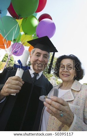 Senior graduate receiving present from wife outside, low angle view - stock photo