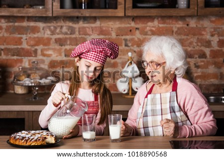 Senior grandmother with granddaughter drinking milk at kitchen