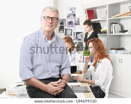Senior graphic designer sitting on desk and working on laptop in studio. Small business. - stock photo
