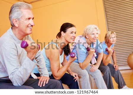 Senior group exercising with dumbbells in a health club