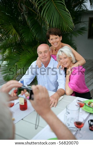 Senior group smiling being photographed by a senior man - stock photo