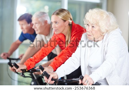 Senior group together in a spinning class in rehab care center - stock photo
