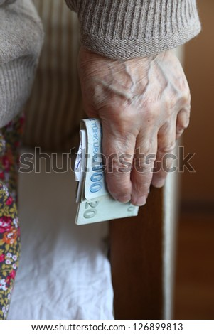 senior hand holding money