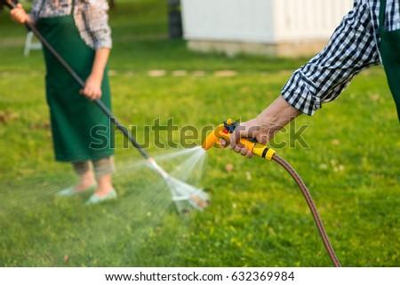 Senior Hand Holding Water Hose. Garden Hose Sprayer. Lawn Care Tips.