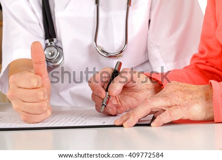 Senior hand signing on the medical examination form - stock photo