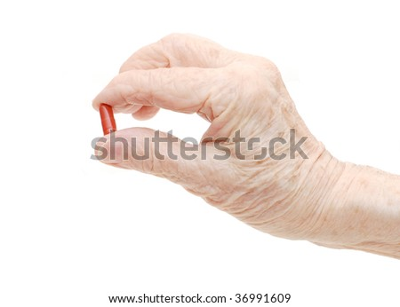 Senior hand with tablets isolated on white - stock photo
