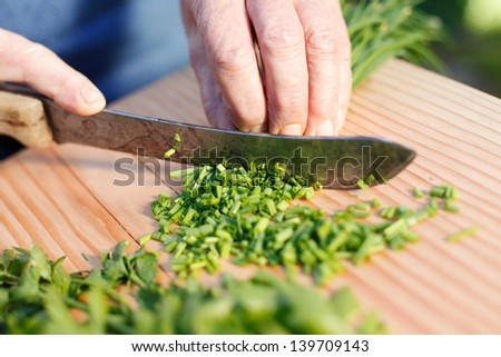 Senior hands cutting fresh chives on the wooden chopping board
