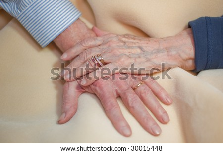 senior hands holding each other