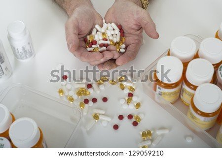 senior hands holding pills with pills on a table and prescription bottles with a white background - stock photo